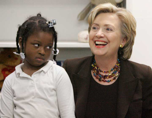 A young Black girl looks skeptically at Hillary Clinton